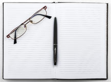 Open notebook with a pen and glasses Stock Image