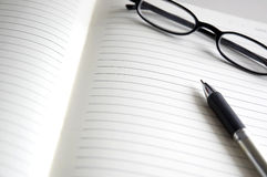 Open notebook with pen and glasses Royalty Free Stock Images