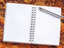 Open notebook with pen on oriental fabric Stock Photography