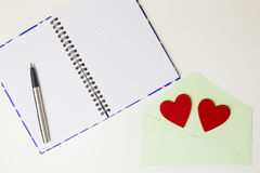 Open notebook, pen, pastel envelope and two red felt hearts on white table. Top view. Stock Photos