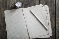 Open notebook, pen and pocket watch on rustic wooden table Royalty Free Stock Images