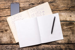 Open notebook with pen and smartphone Stock Image