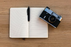 Open notebook with a pen and a vintage film camera, top view on wooden texture Stock Photo