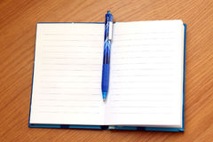 Open Notebook with a pen on a wood table Stock Photography
