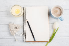 Open notebook, pencil, candle, earpods and tulip Royalty Free Stock Photo