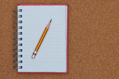 Open notebook and pencil on cork board background Royalty Free Stock Photo