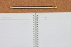 Open notebook and pencil on cork board background Stock Photos