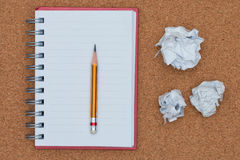 Open notebook and pencil with crumpled paper ball. Stock Image