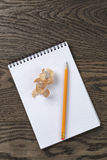 Open notebook with pencil shavings on oak table Royalty Free Stock Photo