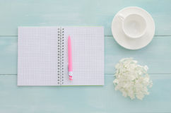 Open notebook with pink pen, coffeecup and hydrangea. Open notebook with pink pen, coffee cup and hydrangea on mint wooden background. Copy space background, top Royalty Free Stock Photography