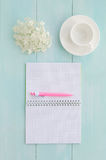 Open notebook with pink pen, coffeecup and hydrangea. Open notebook with pink pen, coffee cup and hydrangea on mint wooden background. Copy space background, top Royalty Free Stock Photo