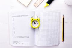 An open notebook-planner with an alarm clock in the center on a white background. Time to do business, copy space. An open notebook-planner with an alarm clock royalty free stock photo