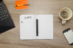 Open notebook with PLANS FOR YEAR 2017. and a cup of coffee on wooden background. stock image