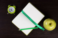 Open notebook with polka dot ribbon and pencil, clock and apple on dark wooden background Stock Photos