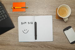 Open notebook with Portuguese words `BOM DIA` Good afternoon and a cup of coffee on wooden background. Top down view stock photography
