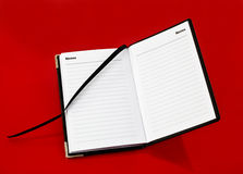 Open notebook on red background royalty free stock photography