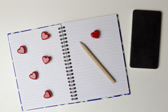 Open notebook with red hearts and mobile phone on white background. Top view Stock Photos
