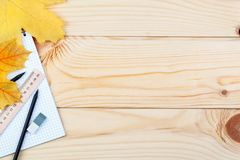 An open notebook and a ruler with two pencils on a wooden background and autumn leaves. School supplies, learning, planning. An open notebook and a ruler with stock image
