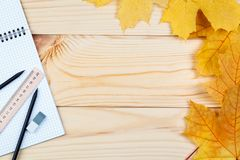 An open notebook and a ruler with two pencils on a wooden background and autumn leaves. School supplies, learning, planning. There is some free space for your stock image