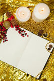 Open notebook, a sheet of paper with Christmas toys, berries and spruce twigs on gold background. Paper for congratulation with Christmas toys, pine cones and Royalty Free Stock Photo