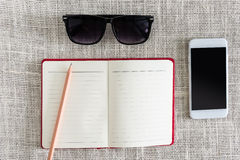 Open notebook, smartphone, sunglasses on clean sackcloth with wo Royalty Free Stock Photography