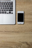 Open notebook and smartphone on wooden background Royalty Free Stock Photos