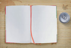 Open notebook and soda can Stock Image