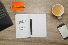 Open notebook with Spanish word `Hola` and a cup of coffee on wooden background. royalty free stock photos