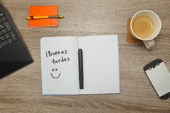 Open notebook with Spanish words `Buenas Tardes` Good Afternoon and a cup of coffee on wooden background. Top down view stock images