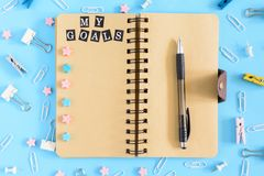 Open notebook on springs with an inscription My Goals. Stationery razrosannye on a blue background. Clerical buttons. Paperclips and asterisks are in disarray royalty free stock photos