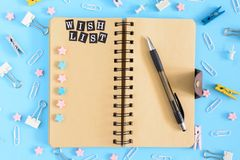 Open notebook on springs with an inscription Wish List. Stationery razrosannye on a blue background. Clerical buttons. Paperclips and asterisks are in disarray stock images