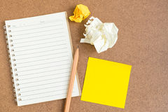 Open notebook with sticky notes and pencil. Top view of open spiral notebook, empty line paper with brown pencil and yellow sticky notes and crumpled paper ball Stock Image