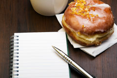 Open notebook, tasty donut and cup of coffee on brown wooden table Royalty Free Stock Image