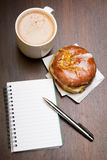 Open notebook, tasty donut and cup of coffee on brown wooden table. Copy space Royalty Free Stock Photography