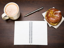 Open notebook, tasty donut and cup of coffee on brown wooden table Royalty Free Stock Photography