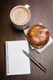 Open notebook, tasty donut and cup of coffee on brown wooden table. Copy space Royalty Free Stock Photo