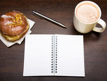 Open notebook, tasty donut and cup of coffee on brown wooden table,. Copy space Royalty Free Stock Photography