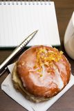 Open notebook, tasty donut and cup of coffee on brown wooden table,. Copy space Royalty Free Stock Photo