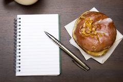 Open notebook, tasty donut and cup of coffee on brown wooden table,. Copy space Stock Photos