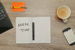 Open notebook with text `BREAK TIME` and a cup of coffee on wooden background. royalty free stock image