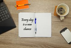 Open notebook with text `Every day is a new chance` and a cup of coffee Royalty Free Stock Photo