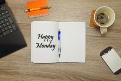 Open notebook with text `Happy Monday` and a cup of coffee on wooden background. Royalty Free Stock Images