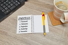 Open notebook with text `Success` and a cup of coffee on wooden background. Royalty Free Stock Photography
