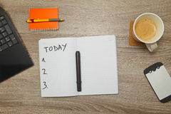 Open notebook with text `TODAY` and a cup of coffee on wooden background. royalty free stock photos