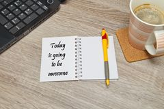 Open notebook with text `Today is going to be awesome` and a cup of coffee on wooden background. stock photography