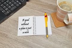 Open notebook with ways to `A goal without plan is just a wish` and a cup of coffee on wooden background. Royalty Free Stock Image