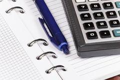 Open notebook on which lies a blue pen and calculator. Stock Photos