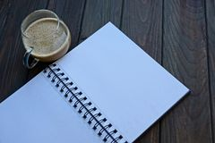 Open notebook with white pages with a cup of coffee on the table. Open notebook with white pages with glass cup of coffee on the table Royalty Free Stock Photography
