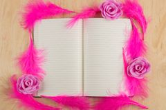 Open notebook with white pages and pink feathers on a wooden tab. Open notebook with white pages and pink feathers around on a wooden table Stock Photography