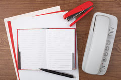 Open notebook and white phone on wooden texture Royalty Free Stock Photography